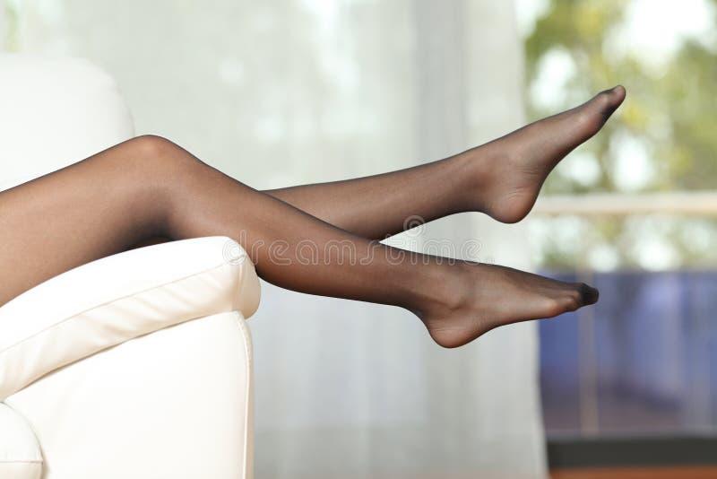 Женские ножки в нейлонах на диване стоковое фото rf