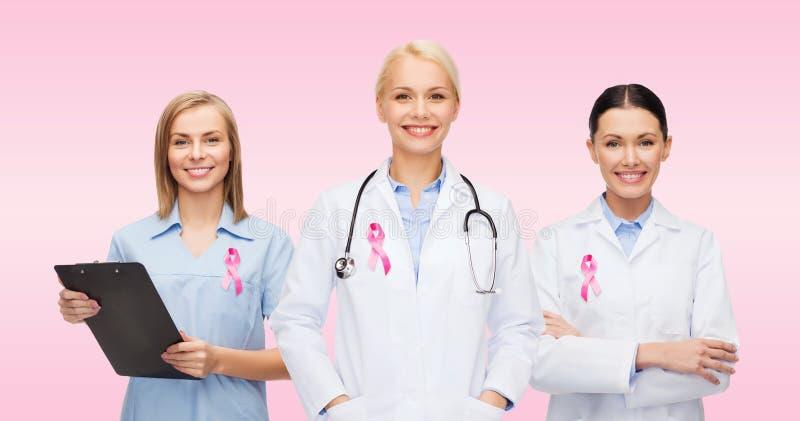 Женские доктора с лентой осведомленности рака молочной железы стоковые фотографии rf