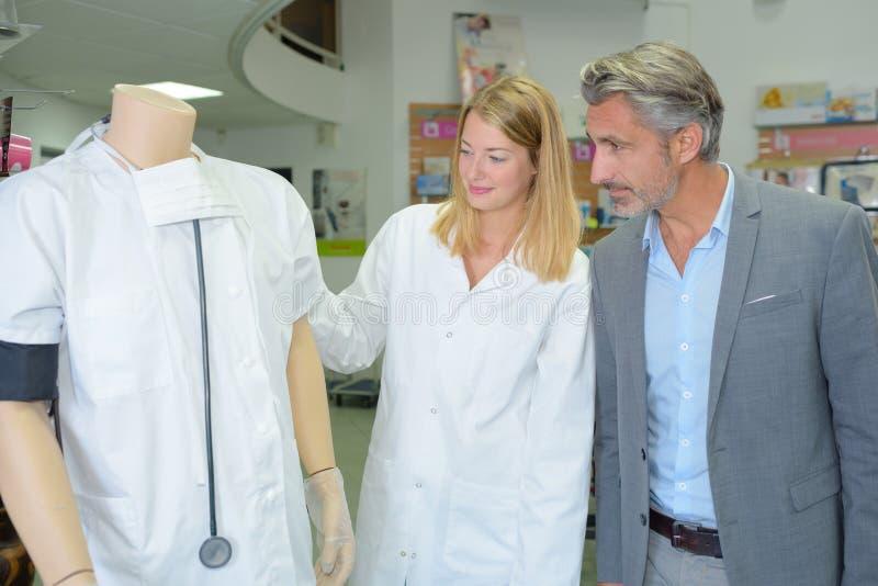 Женские покупки продавца и клиента в профессиональном магазине одежд стоковая фотография