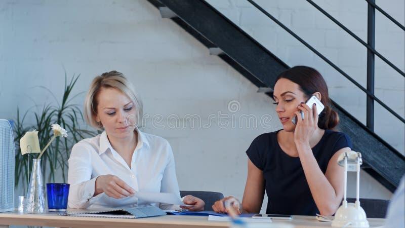 Женские работники работают в офисе, имеющ телефонные звонки и обработку документов стоковое изображение