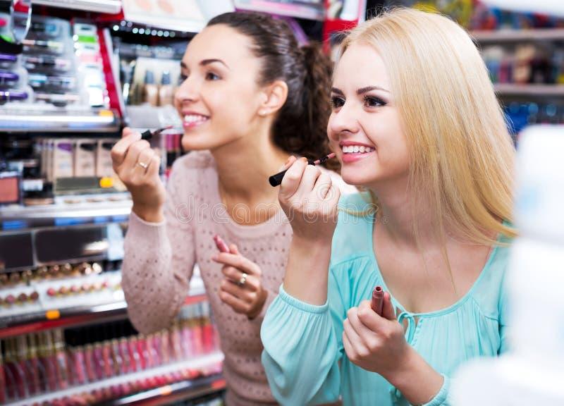 Женские друзья выбирая лоск губы стоковое изображение rf