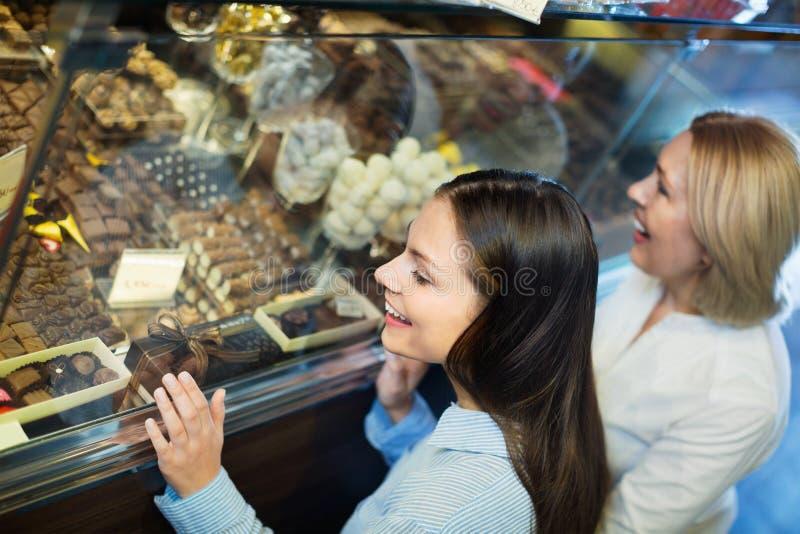 Женские друзья выбирая точные шоколады и кондитерскаю стоковое фото