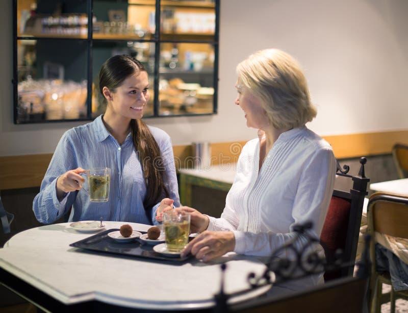 Женские друзья говоря на таблице и усмехаться кафа стоковые изображения rf