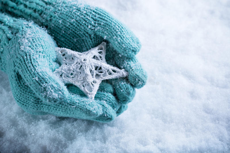 Женские руки в светлом teal связали mittens с entwined белой звездой на белой предпосылке снега Концепция зимы и рождества стоковое изображение