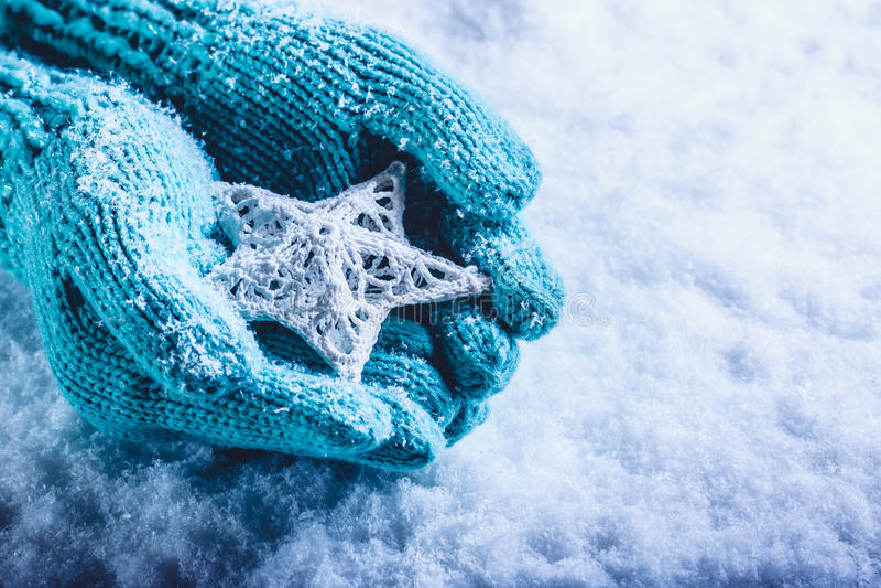 Женские руки в светлом teal связали mittens с entwined белой звездой на белой предпосылке снега Концепция зимы и рождества стоковые изображения