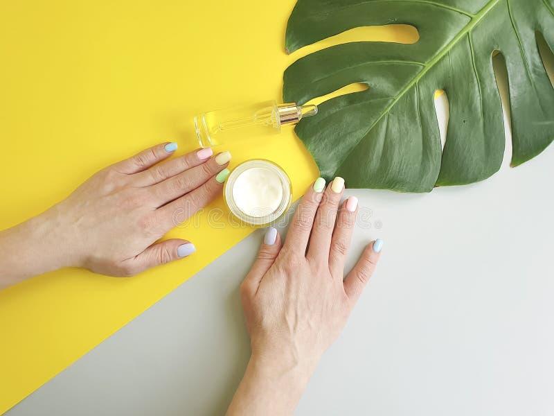 Женские руки делают маникюр, лето сливк косметической сути гигиены творческое, лист monstera на бумажной покрашенной предпосылке стоковая фотография rf