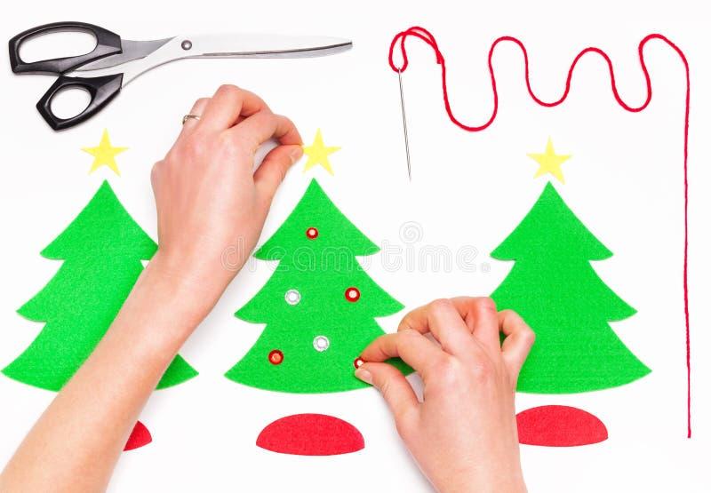 Женские руки делая поздравительные открытки рождества на белизне стоковые изображения rf