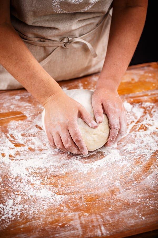 Женские руки делая тесто хлеба стоковая фотография