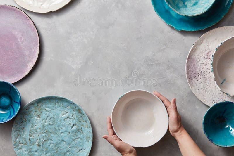 Женские руки держат белый керамический шар на серой мраморной таблице Глина handcraft шары, плиты различных размеров пуста стоковая фотография