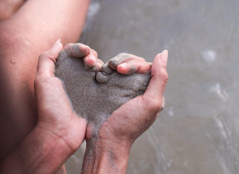Женские руки держат песок в форме сердца стоковое изображение rf