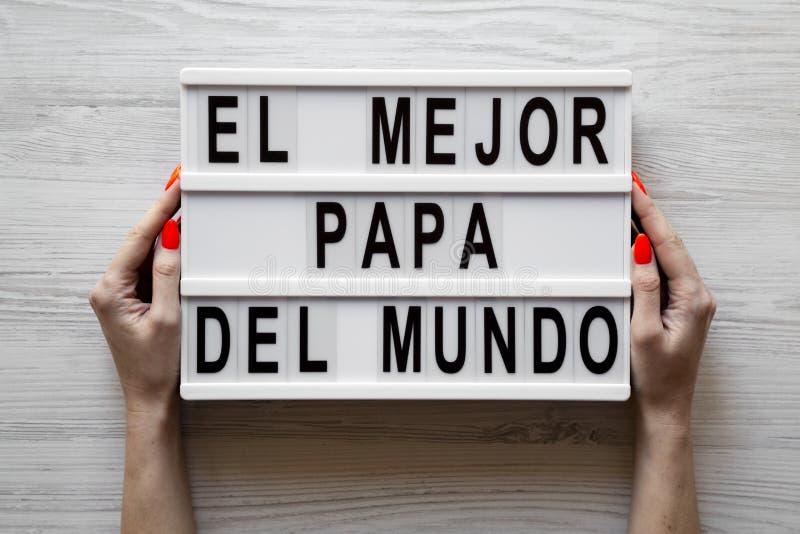 """Женские руки держат lightbox с """"El словами Mejor Папы Del Mundo """"над белой деревянной предпосылкой r стоковое фото"""