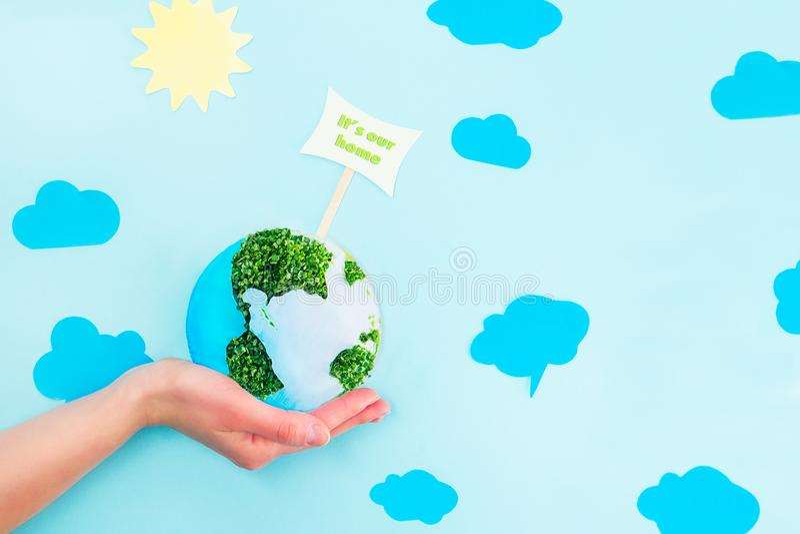 Женские руки держа бумагу земли и коллаж ростков зеленого цвета моделируют с ним ` s наш домашний указатель на голубой предпосылк стоковое фото