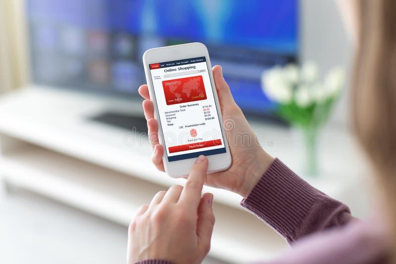 Женские руки держа касание пальца покупок app телефона онлайн оплачивают стоковое фото