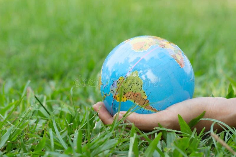 Женские руки держа плавая землю на естественной зеленой предпосылке коричневейте покрытую землю дня относящое к окружающей среде  стоковое фото