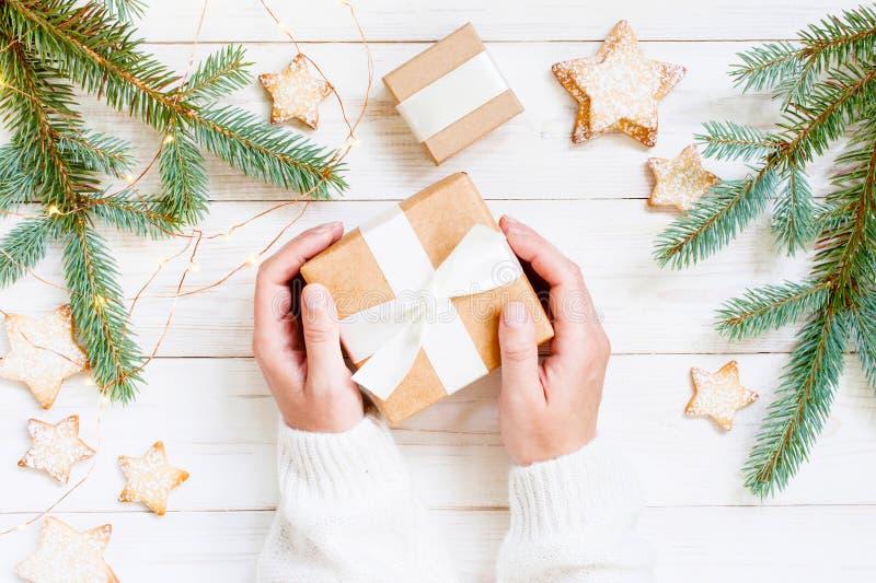 Женские руки держа подарок рождества, белый деревянный стол стоковые фото