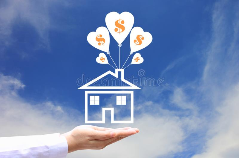 Женские руки держа символ дома с воздушным шаром и символ доллара на предпосылке голубого неба, сохраняют деньги для подготавлива стоковое изображение rf