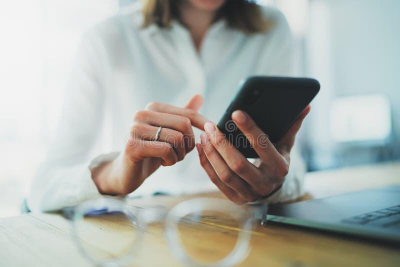 Женские руки держа смартфон и касаясь экран Коммерсантка используя мобильный телефон Крупный план на запачканной предпосылке стоковые изображения rf