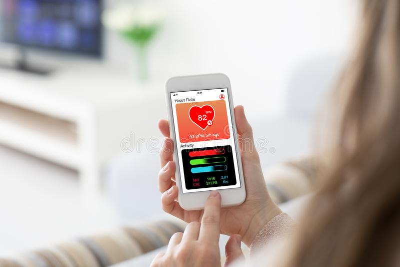 Женские руки держа телефон при здоровье app отслеживая scr деятельности стоковые фотографии rf