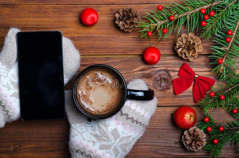Женские руки держа чашку с горячим питьем и ove smartphone стоковое изображение