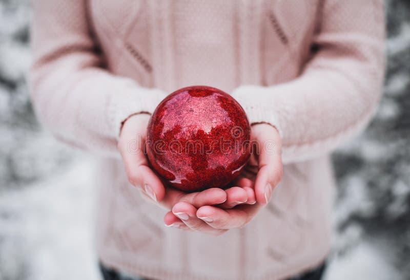 Женские руки держа шарик красного цвета рождества Морозный зимний день в снежном Новом Годе леса с Рождеством Христовым и счастли стоковая фотография