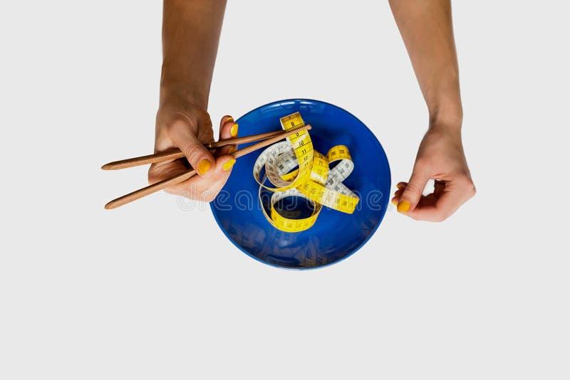 Женские руки держа китайские палочки и плиту при лента измерения изолированная на белой предпосылке стоковое фото