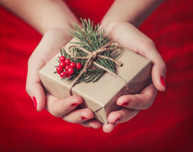 Женские руки держа подарочную коробку рождества с ветвью ели, сияющей предпосылки xmas Праздничный подарок и украшение стоковое фото rf