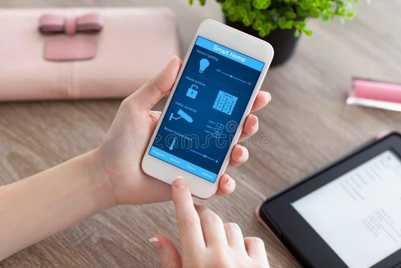 Женские руки держа телефон с домом app умным на экране стоковые фотографии rf