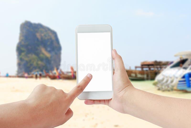 Женские руки используя мобильный телефон на запачканной предпосылке пляжа стоковые фото