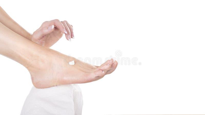 Женские руки и поднимающее вверх ноги близкое Женщина прикладывая moisturizing сливк на ее ногах Принципиальная схема внимательно стоковая фотография rf