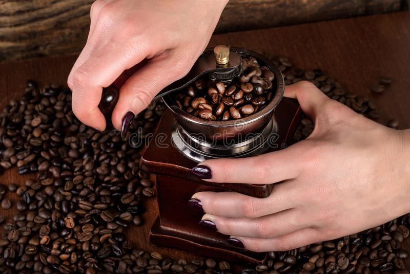 Женские руки меля зажаренные в духовке кофейные зерна в старой ретро мельнице стоковое фото