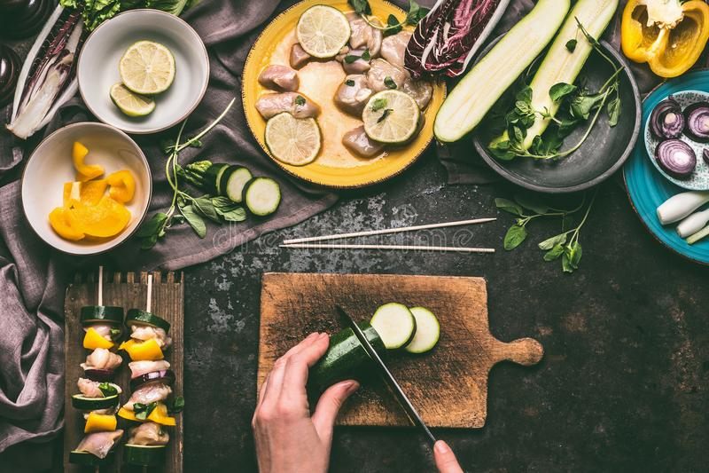 Женские руки отрезали овощи для протыкальников мяса делая на деревянной предпосылке кухонного стола с частями цыпленка стоковые изображения