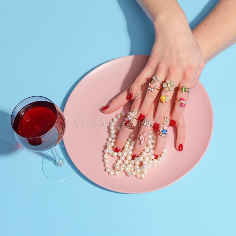 Женские руки отрезали шарики жемчуга с ножом и вилкой в розовой плите на голубой таблице принципиальная схема творческая Взгляд с стоковое фото