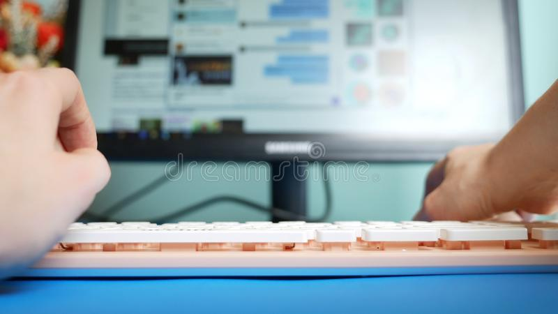 : : Женские руки печатая на сообщениях розовых клавиатуры в социальных сетях, на фоне стоковое фото