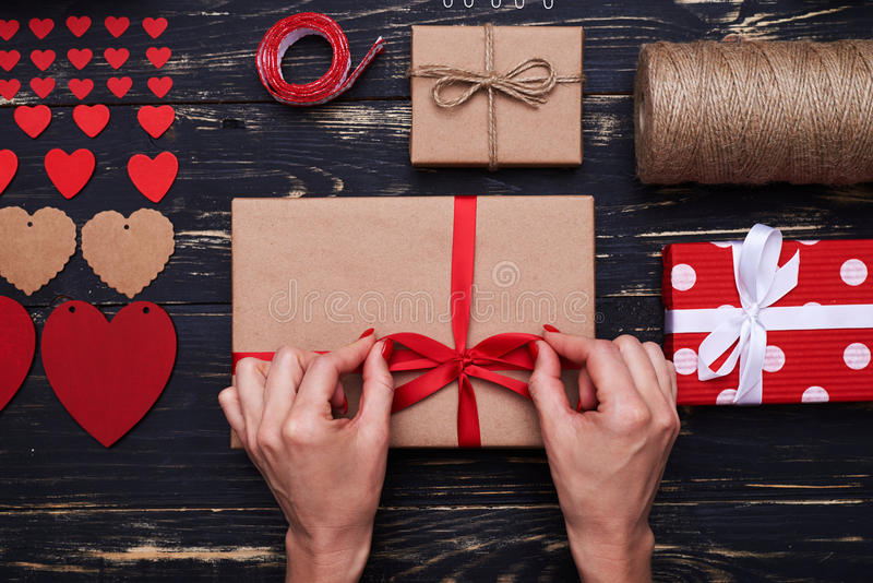 Женские руки связывают бабочку ленты на обернутой подарочной коробке стоковая фотография rf