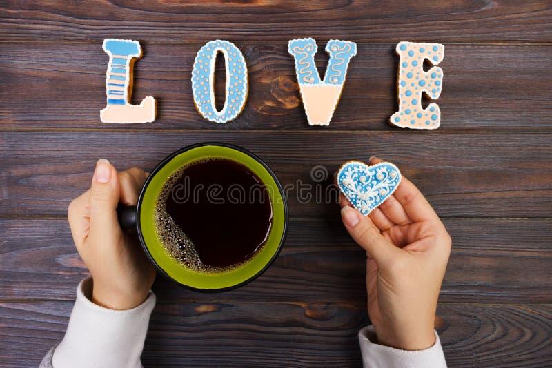Женские руки с кофе и сердцем сформировали печенья на деревянном столе, взгляд сверху человек влюбленности поцелуя принципиальной стоковое изображение rf