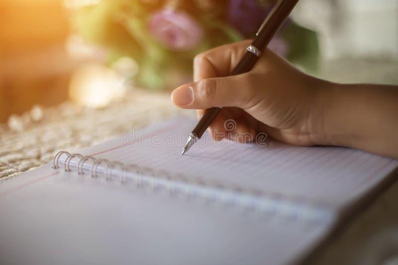 Женские руки с сочинительством ручки на тетради стоковая фотография rf