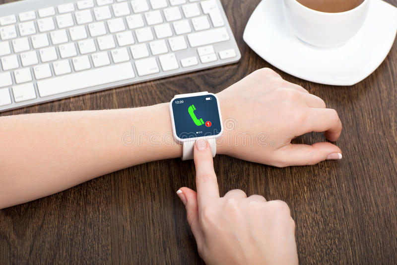 Женские руки с smartwatch с телефонным звонком стоковые изображения