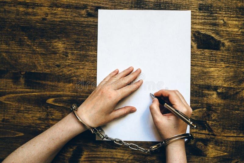 Женские руки cuffed исповедь подписания, взгляд сверху стоковые изображения