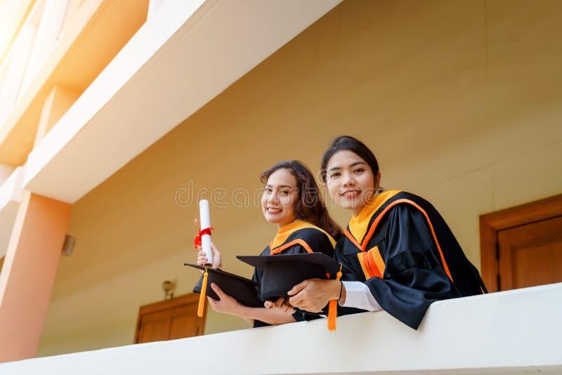 Женские студент-выпускники университета празднуют счастливо после завершенный и получили сертификат степени диплома во вступитель стоковые изображения rf