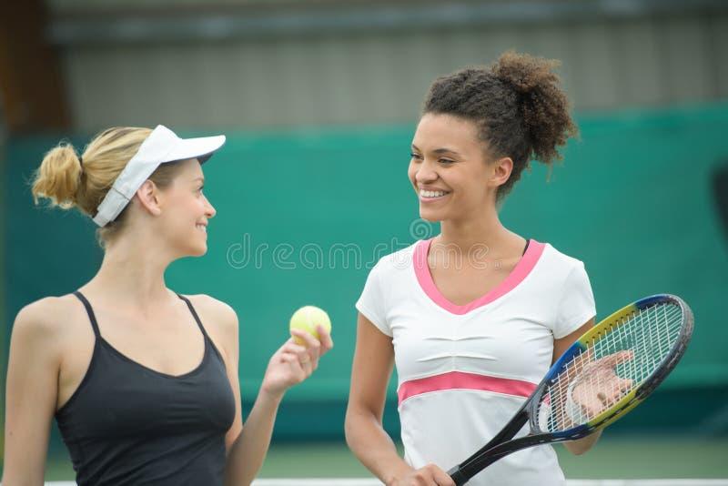 Женские теннисисты говоря на суде глины стоковая фотография
