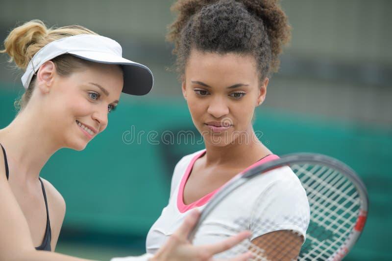 Женские теннисисты проверяя ракетку стоковые фотографии rf