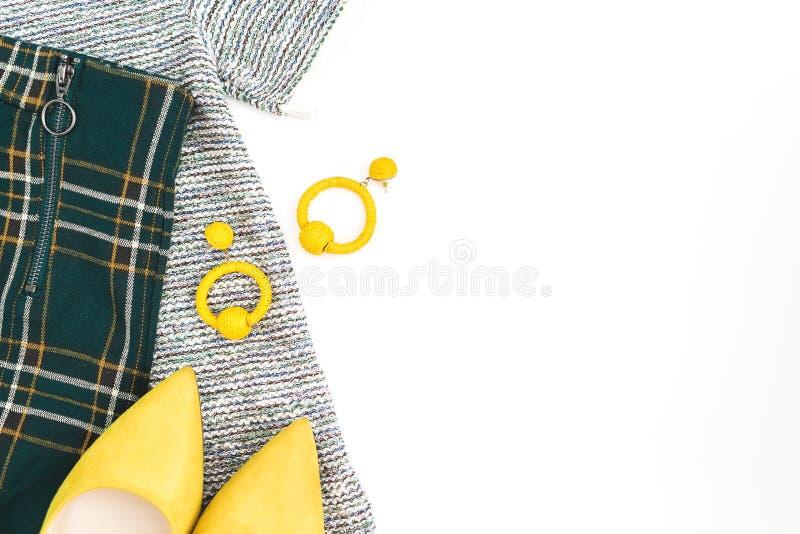 Женские ткань и аксессуары моды Желтые ботинки, серьги, свитер и брюки на белой предпосылке Плоское положение, взгляд сверху стоковое изображение rf