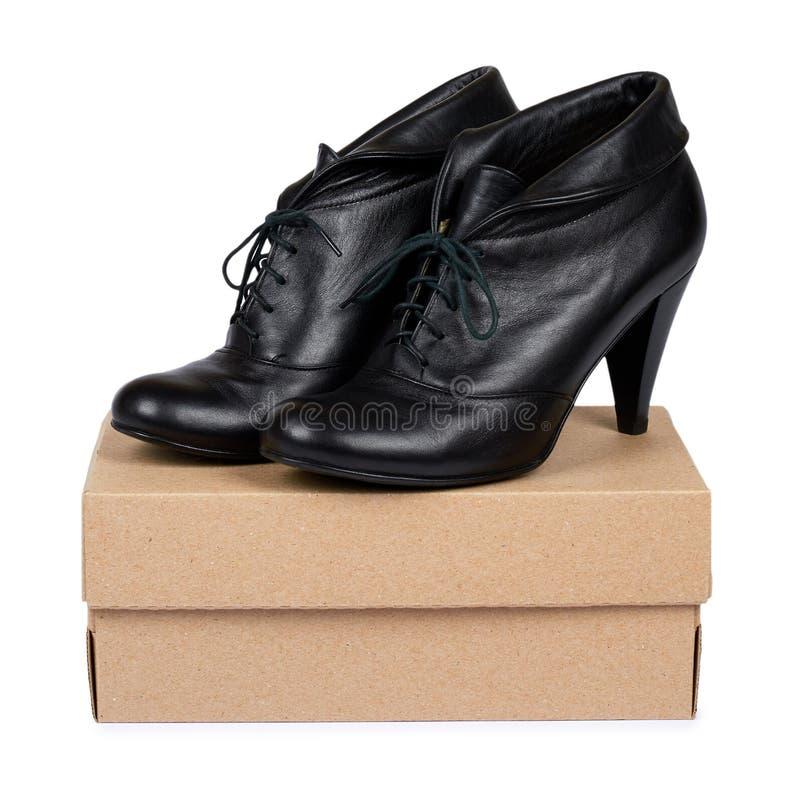 Женские черные кожаные ботинки высокой пятки при коробка изолированная на белой предпосылке стоковые изображения rf