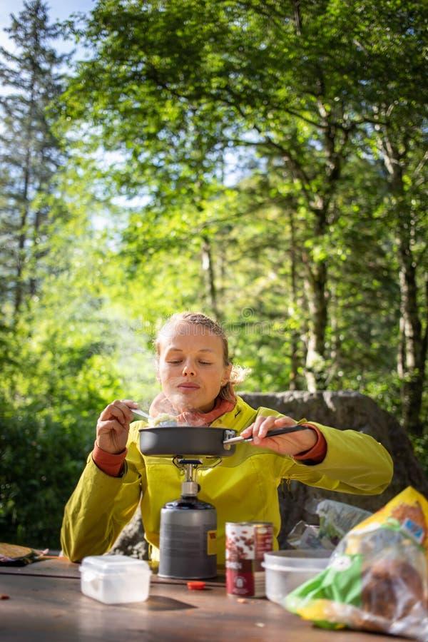 Женские hiker/альпинист подготавливая ужин на газовой горелке стоковая фотография