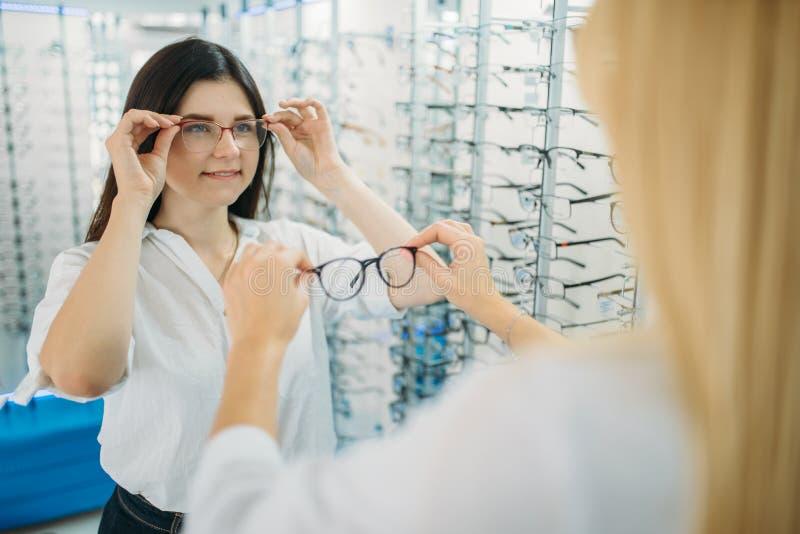 Женские optician и покупатель выбирают рамку стекел стоковая фотография rf