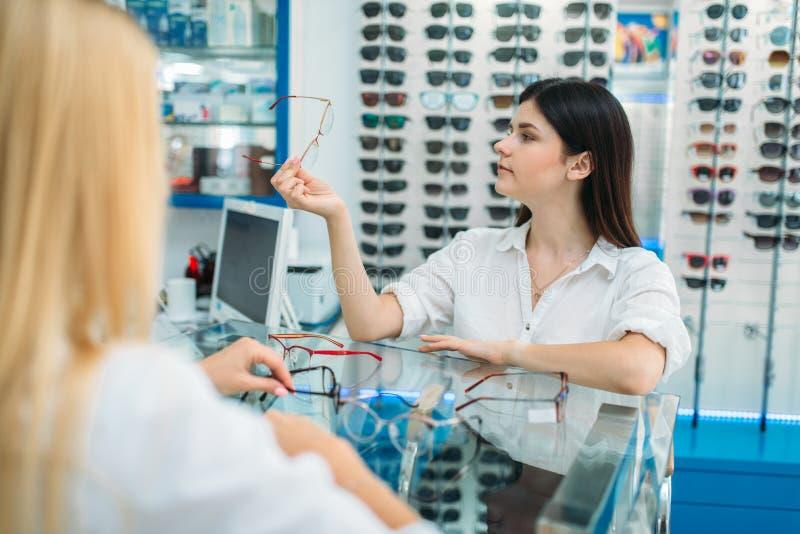 Женские optician и потребитель выбирают рамку стекел стоковое фото