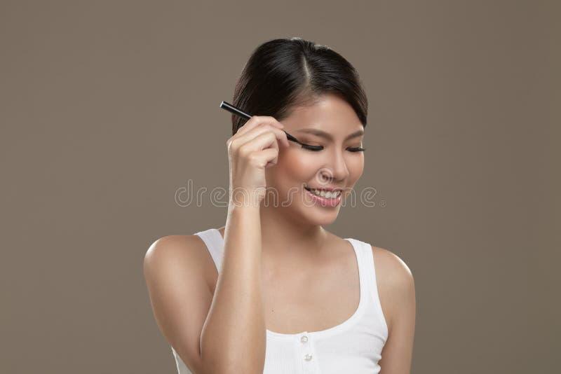 Женский азиат прикладывая вкладыш глаза стоковое изображение rf