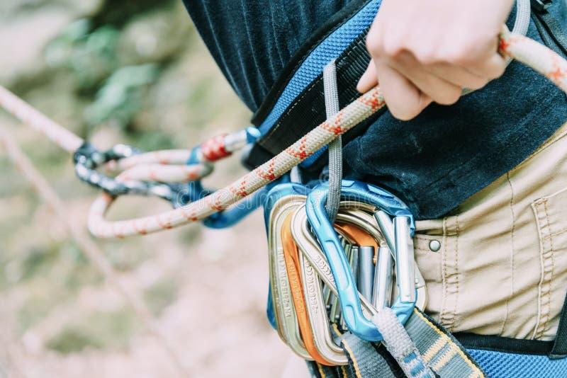 Женский альпинист belaying с веревочкой и диаграммой 8 стоковые изображения rf