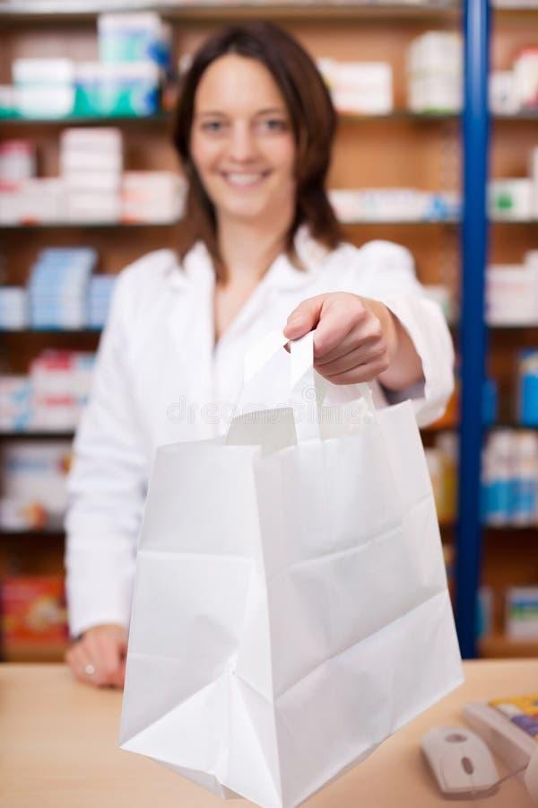 Женский аптекарь давая медицину к клиенту стоковое изображение rf
