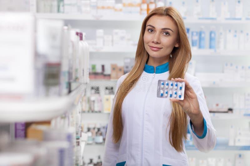 Женский аптекарь работая на ее аптеке стоковые изображения